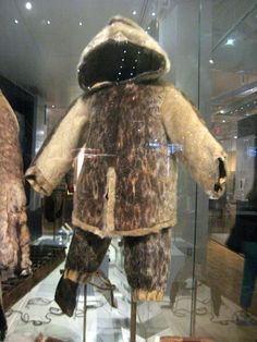 """1910-1914 Inuit (First Nations) Boy's parka and pants at the Royal Ontario Museum, Toronto - From the curators' comments: """"The Inuit seamstress has used the natural colouring and patterns of the ringed sealskin to pleasing effect. The front and back sections of the parka are each made of one skin. The dark colouring of the seal's back forms the parka's front and back sections which fade to the lighter stomach colouring on the sides."""""""
