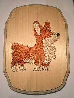 This handmade brown Corgi is made with a very minimal design! Hand crafted with love, its only made of nails and string! The wooden plaque is a