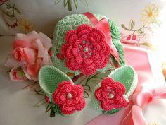 Cappellino e scarpine eseguiti a mano all'uncinetto in cotone verde chiaro con fiori fucsia applicati. Crochet moda bebè estate