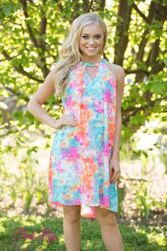 This vibrant tie dye dress is perfect for your next road trip or festival weekend! Featuring neon orange, neon pink, teal, white, purple, and blue, the colors alone are super bright and light! The dress itself is also very airy, with a racerback, no sleeves, and a cute v-shaped cut out detail and metallic button in the front.