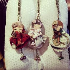 ..Colgantes-Broches... These cute little things look they their dresses are made from fabric yo yos.