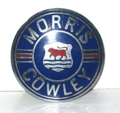 """Morris Car Badge - Morris Cowley Flatnose 1927/30. 2¼"""" Diameter. This badge is 'Tail Up' and is fixed to the radiator grille by a single stud. No maker's mark. The 1930 onwards cars had a different shaped badge with wings. This one differs in appearance from the Bullnose Cowley badge by a horizontal red line separating the words Morris and the Cowley."""