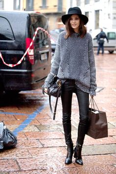 black fedora, chunky nit sweater, black pants and boots traveling outfit