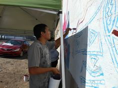 Cristian fills in the shapes for phase 2 of the outdoor mural.