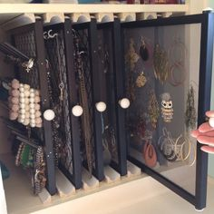 done by the poster. neat idea ----We took some empty cabinet space in my sister's bathroom and created jewelry displays using picture frames, hooks, fabric, drawer pulls, window screen material, spool holders and trim (for the guides in the cabinet). Cute and easy!