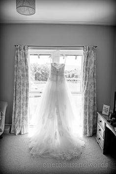 91ff1e28a5c Lace wedding dress hangs in window on Dorset home wedding morning.  Photography by one thousand