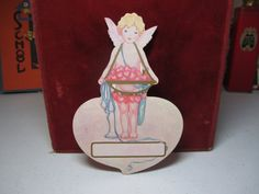 1920's unused Dennison die cut valentine place card cupid with bow and arrows slung over his shoulder and holds tray of pink hearts