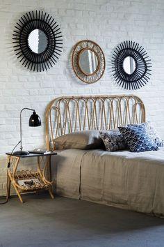 Tête de lit en rotin, son chevet avec plateau noir et les miroirs vintage KOK MAISON