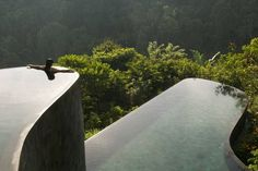 Inmitten der steilen Reisterrassen Balis liegt der große Panorama-Pool des Hotels Ubud Hanging Gardens. Er ist terrassenförmig angelegt und erstreckt sich über zwei Ebenen. Mit seiner natürlich geschwungenen Silhouette und seinem klaren Wasser in gedämpften Blau-Grün-Tönen passt er perfekt in die tropische Umgebung.