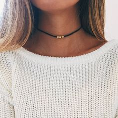 "Simple antique gold tibetan triple bead on a 12-14.5"" cotton choker with an adjustable hook for closure."
