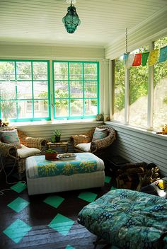Boho enclosed patio - lovely turquoise and Tibetan prayer flags.