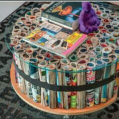 Magazines rolled up and holds up the glass top to make a coffee table. So Creative!