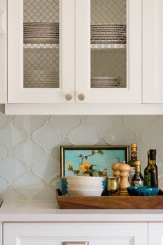 white kitchen with Caesarstone Frosty Carrina countertops, arabesque tile backsplash, chicken wire cabinet fronts, mixed hardware