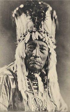 circa 1925 Siksika Chief Curly Bear wearing war bonnet and traditional beaded shirt .