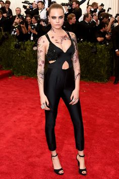 2015 Met Gala: Cara Delevingne is wearing a black cutout Stella McCartney jumpsuit with a sparkle bralette. I adore this jumpsuit. It fits Cara perfectly! I like the tats to add some Cara edge! Cara Delevingne Tattoo, Cara Delevigne, Cara Delevingne Style, Punk Rock Outfits, Mode Outfits, Gala Dresses, Red Carpet Dresses, Nice Dresses, 2015 Dresses