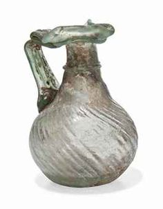 A ROMAN GREEN GLASS JUG  CIRCA 3RD-4TH CENTURY A.D.  With trefoil lip, the handle folded to form a thumb rest, the body with diagonal ribbing, applied trail around neck and under rim  4½ in. (11.5 cm.) high