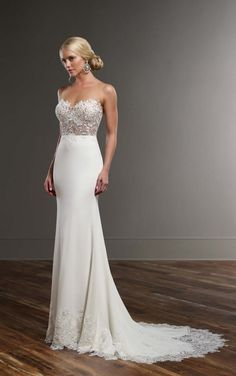 This sleek and sexy designer Martina Liana wedding gown features fine, natural lace and a sexy illusion back that zips up under fabric-covered buttons. The skirt is made from rich Bellagio crepe and falls elegantly into a court train that is embellished with scalloped lace.