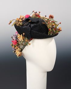 The doll hat and snood forms were extremely popular in the late 1930s and early '40s. The snood in particular because it served both a functional and decorative purpose by stylishly controlling women's hair while they worked during wartime. This example, however, is purely decorative. The flowers used by Schiaparelli to decorate the straw and veiling show a particular naturalism, variety and detail which indicate its couture quality. The black and navy blue combination is also very chic.
