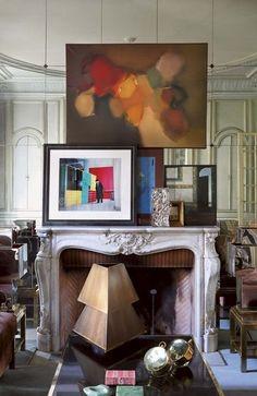 Salon avec cheminée décorée de tableaux d'artiste chez Willy Rizzo - Un appart' haussmannien au look excentrique - CôtéMaison.fr