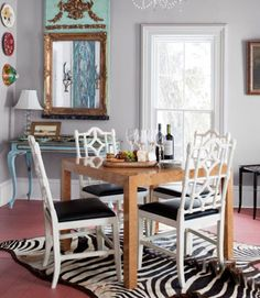 This eclectic Indiana farmhouse's dining room's myriad treasures include an Italian chandelier and a midcentury Parsons table, clad in bird's-eye maple veneer. The owner purchased the 1940s Louis XVI-style mirror and console at an estate sale, and found the zebra rug at an antiques store.