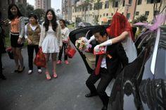 Un novio saca a su novia sobre su espalda de un auto como parte de una tradición el día de su boda en Wuhu, provincia de Anhui. En ciertas partes de China creen que los pies de la novia no deben tocar el suelo, por lo que los familiares de la novia y el novio se turnan para llevar a la novia desde el momento en que sale de su cama hasta que llega a la casa del novio.  País: China