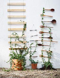 Flere espalierer i metall henger på en vegg med planter i små glasskolber.