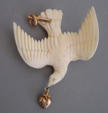 VICTORIAN  bird  		pendant beautifully carved with 9 ct yellow gold  		fittings, tiny heart with a gypsy set pearl in it�s mouth, circa late  		1800s, 2-1/8 by  		1-3/4. This recalls the story of the dove who brought a leaf to  		Noah's ark signaling the end of the flood, a symbol of hope.