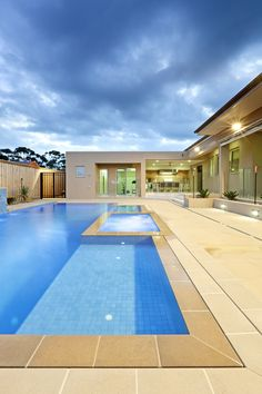 big courtyard pool and spa with smart dual slot wet deck drain. pool is finished with mid blue tiles and anston sorrento paving