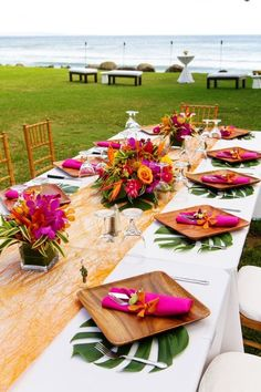 Destination wedding idea - outdoor, tropical wedding reception - rectangle tables with leaf place mats, wooden plates and hot pink napkins {MeewMeew Studios}