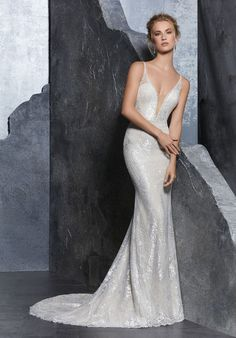 This Mori Lee Bridal 8201 Kendra fitted bridal dress features a plunging illusion neckline, with braided spaghetti straps that split down the open back. This metallic embroidered bridal gown features covered buttons over the back zipper, and flares softly to a scalloped hem and court train. Dainty beadwork trims the notched bodice and waistline. Available in sizes 0 to 28.