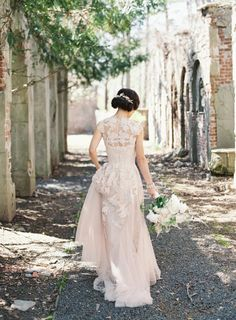a blush wedding dress with cap sleeves, lace appliques and an illusion neckline