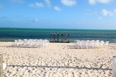 Decorated tiki torches and chairs set out for a beautiful Smather's Beach Wedding in Key West, Florida! Gorgeous whites sands!