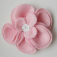 Adorable pale baby pink hat with fleece flower. Quality pink fleece with matching flower (attached by velcro for easy removal for washing). The flower has a white button center. This hat is sure to look adorable on your little one. Great for a new baby gift or for those special photos. This is so sweet on a little one.  Select size when ordering Measure around the head just above the ears. Newborn - to 15 0-3 month - to 16 3-12 month - to 18 1-3 years - to 19.5 2-6 year - to 21 4-8 year - to…