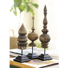 Set of 3 Wood Sculptures  These exotic, turned mango wood sculptures were inspired by the finials crowning the houses and temples of Thailand. Cracks and fissures occur naturally in the wood and enhance their great character. Antique Burn finish with black stepped weathered wood base.
