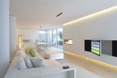 All-white interior in this ultra modern space includes walls with embedded lighting at ceiling and floor, holding both black media strip and horizontal gas fireplace. Light hardwood flooring throughout supports an array of white furniture, including plush sectional, matching ottoman, and dining table sunlit via full height glass.