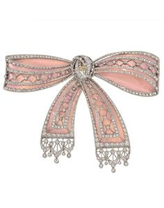 A Belle Epoque platinum, gold, enamel and diamond bow brooch, French, circa 1910. Designed in pink enamel with old mine and rose-cut diamond accents, in platinum and 18k yellow gold, the back with elegant foliate patterned engraving in yellow gold. 2.75 x 2 inches. #BelleÉpoque #brooch