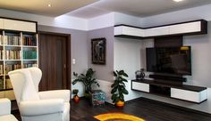 Kolem celého obývacího pokoje probíhá na stěnách světle šedý pruh výmalby, na který navazuje veškerý nábytek vmístnosti