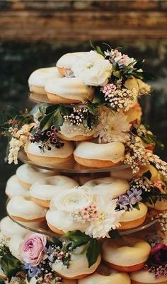 Do you love this glazed donut cake tower? We do! We love the perfectly placed floral design. Seriously, can someone bring us some donuts?? #hungry #donuts #donutcaketower #weddingideas #fallwedding #winterwedding #desserttable #weddingcake