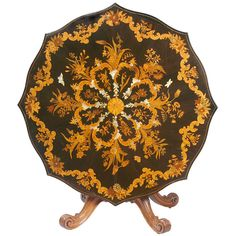 Large Victorian Marquetry Center Table  COUNTRY: England  CREATION DATE: Circa 1850-1860  MATERIALS: The top with satinwood, tulipwood and mother of pearl inlay on a ebony ground the base in solid mahogany