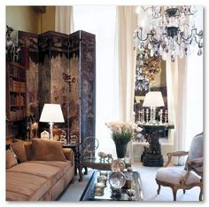 Coco Chanel's Paris Apartment: The tall screen looming over the low sofa, abat jours and chandelier, muted tones.