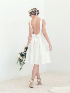 Tory is a modern backless short wedding dress with a square neckline and a full pleated skirt. Its beautifully cut low back combines with the elegance of luxurious silk taffeta and the refinement of its simple silhouette. The silk taffeta we are using for this dress has a subtle sheen and pleasant crispiness, without feeling stiff. The color is a soft white. This dress feels almost weightless, yet it fits snuggly in the bodice to give you the confidence you want on your big day. The bodice…