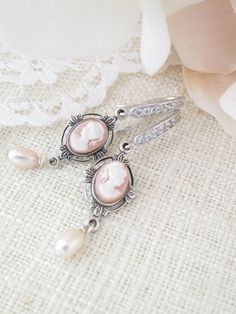 Bring a sweet blush of color and vintage appeal with this feminine cameo earring. The finishing touch to this romantic antique silver dangle is a dainty freshwater pearl that sways gently.