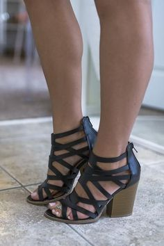 Black heels feature a wooden chunky heel, caged strappy details, and a zipper back Heel height is 4 in