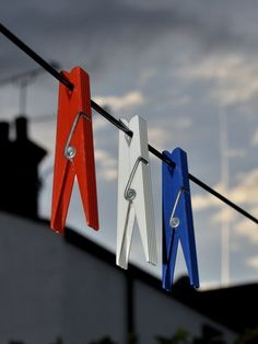 three plastic pegs in red white and blue formation to be used for drying Olympic kits and towels.