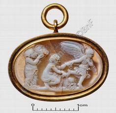 """camée, """"Figure féminine ailée fuyant une ménade et un silène"""" (camée.63), BnF. Calcédoine, époque romaine.  Au centre, une ménade, à demi-nue, les jambes enveloppées dans son manteau, est accroupie devant un panier qu'elle vient de découvrir. De la main gauche, elle cherche à retenir une figure féminine ailée qui s'enfuit en faisant de la main gauche un geste d'horreur. Celle-ci est vêtue d'un chiton court ceinturé à la taille. A gauche, un silène, debout, vêtu d'une draperie autour des…"""