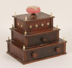 "19th century three tiered wooden sewing box with ivory accents; pin cushion form lift off top, two drawers below, ivory finials and grommets. 8 1/2""H."