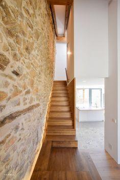 Escalera iluminada junto a muro de piedra | Reforma en Ávila, España | METRIA Arquitectos