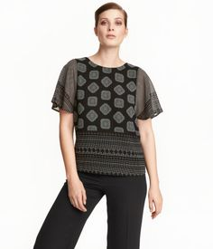 Black. CONSCIOUS. Straight-cut blouse in airy woven fabric with a printed pattern. Short, wide sleeves, V-neck opening at back, and tie at back of neck.