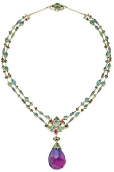 Art Nouveau necklace by Louis Comfort Tiffany of Tiffany & Co., circa 1914-1927. It features a double-chain of small fancy-shaped links applied with champlevé enamel in shades of blue, green and plum, spaced at intervals by cabochon emeralds. The center of the chain is decorated with a large floral link enameled in blue and green and set with cabochon sapphires, rubies, and an emerald.