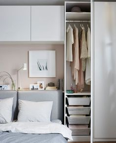 A sofa bed is made up for sleeping, and the storage next to it is opened to reveal clothes within.